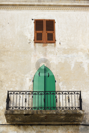 Traditional, town house balcony in Calvi Corsica stock photo, A traditional, town house balcony and old wood door in Calvi Corsica by Mark Yuill