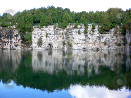 Quarry cliff with reflection stock photo,  by J.G. Byers