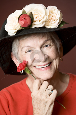 Senior woman in a hat with flowers stock photo, Senior woman in a red shirt and hat with flowers by Scott Griessel