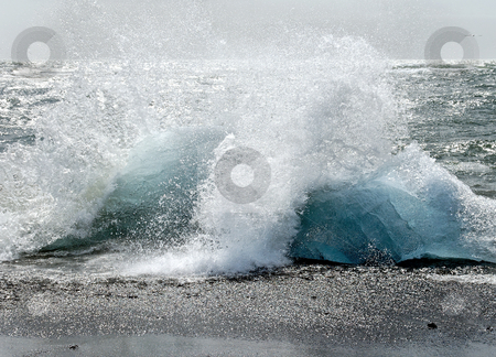 Ice floes on the beach stock photo, Splashing waves on bluegreen segements of glacier ice by Wino Evertz