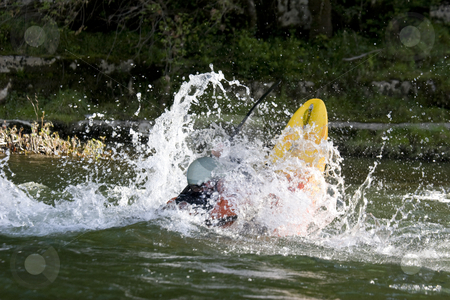 Dynamic white water kayak action stock photo, Expert white water kayak paddler performing tricks by Mark Yuill