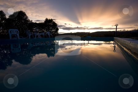 Reflection of sunset over swimming pool  stock photo, Reflection of sunset over swimming pool in france by Mark Yuill