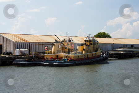 Two tugboats stock photo, Two yellow, red, and black tugboats moored at a rusty dock by Lee Barnwell