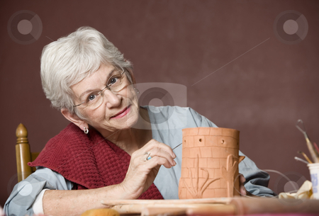 Woman working with clay stock photo, Senior woman working on a clay sculpture by Scott Griessel