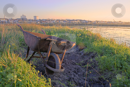 A rusty wheelbarrow stock photo, A rusty wheelbarrow abondon with the city in the background by Paulo Resende