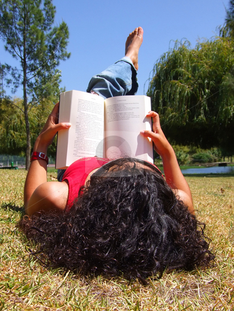 Woman reading book in park stock photo, Young girl reading book in park by Paulo Resende