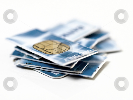 Credit card in pieces stock photo, Credit card cut in pieces on  reflective white surface by Laurent Dambies