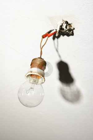 Light bulb hanging from bare wires stock photo, Light bulb hanging from bare wires with shadow by Mark Yuill