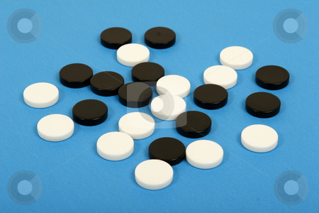 Black and white counters  stock photo, Black and white counters on blue background by Mark Yuill