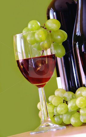 Red wine with green grapes stock photo, Red wine glass with grape and bottle over green by Julija Sapic