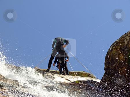 Men preparing to descend stock photo, Men preparing to descend waterfall by Paulo Resende