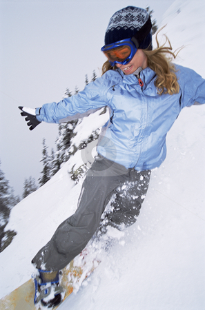 Young woman snowboarding stock photo,  by Monkey Business Images