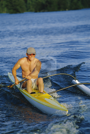 Man canoeing at sunset stock photo,  by Monkey Business Images