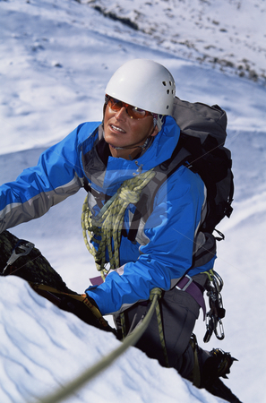 Young man mountain climbing on snowy peak stock photo,  by Monkey Business Images