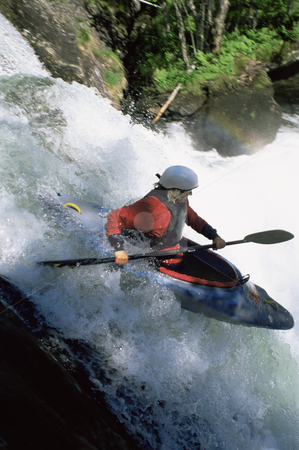 Young woman kayaking down waterfall stock photo,  by Monkey Business Images