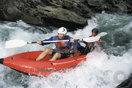 Two people paddling inflatable boat down rapids stock photo,  by Monkey Business Images