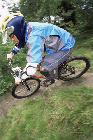 Young man mountain biking stock photo,  by Monkey Business Images