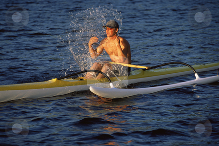 Man refreshing while canoeing stock photo,  by Monkey Business Images