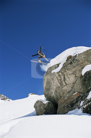 Skier jumping  stock photo, Skier jumping off mountain ledge by Monkey Business Images