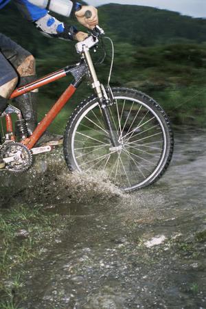 Mountain biker crossing stream stock photo, Mountain biker crossing stream by Monkey Business Images
