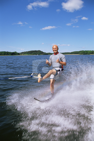 A young man water skiing stock photo,  by Monkey Business Images