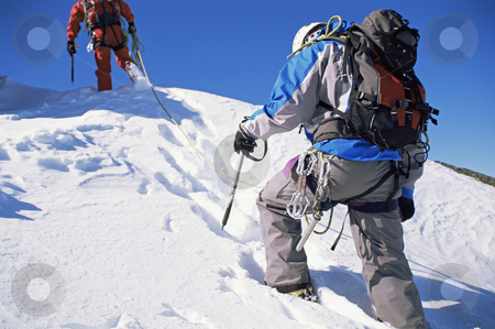 Young men mountain climbing on snowy peak stock photo, Young men mountain climbing on snowy peak by Monkey Business Images