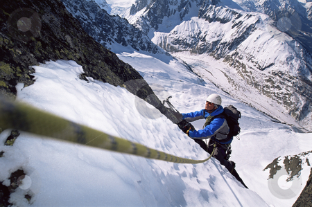 Young man mountain climbing stock photo, Young men mountain climbing on snowy peak by Monkey Business Images