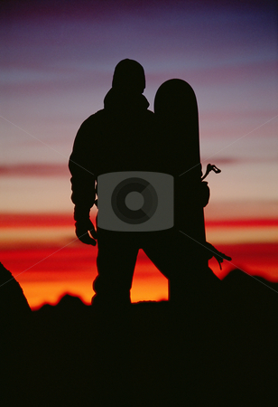 Silhouette of  snowboarder against sunset stock photo,  by Monkey Business Images