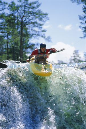 Young man kayaking on waterfall stock photo,  by Monkey Business Images