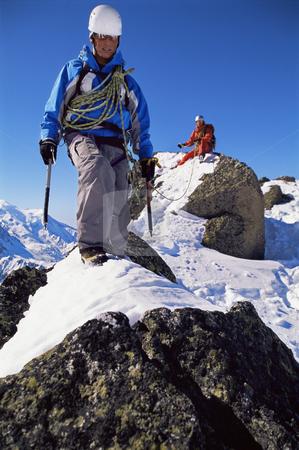 Young men mountain climbing stock photo, Young men mountain climbing on snowy peak by Monkey Business Images
