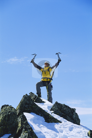 Mountain climber stock photo, Young man celebrating reaching the top of a mountain by Monkey Business Images