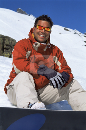 Young man taking a break from snowboarding stock photo,  by Monkey Business Images