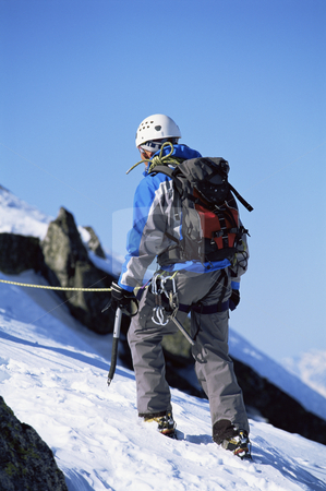 Young man mountain climbing on snowy peak stock photo, Young man mountain climbing on snowy peak by Monkey Business Images
