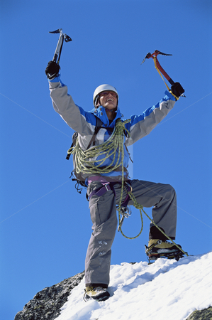 Young man celebrating on snowy peak stock photo, Young man celebrating on snowy peak by Monkey Business Images