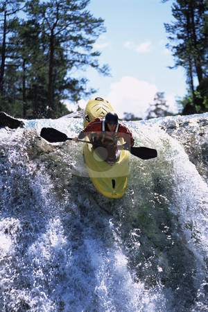 Young man kayaking down waterfall stock photo,  by Monkey Business Images