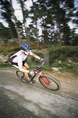 Young woman mountain biking stock photo, Young woman mountain biking down dirt road by Monkey Business Images