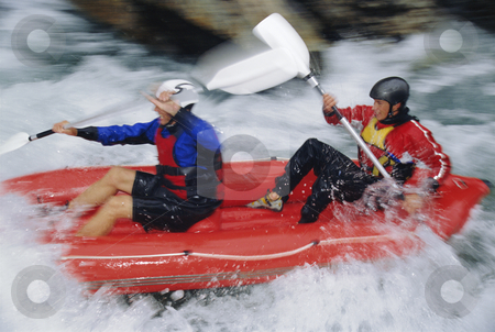 Two people white water rafting stock photo, Two people paddling inflatable boat down rapids by Monkey Business Images