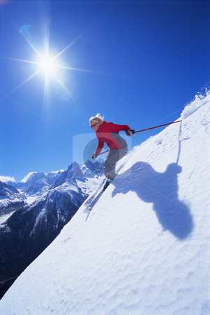 Young woman skiing stock photo, Young woman skiing down mountain slope by Monkey Business Images