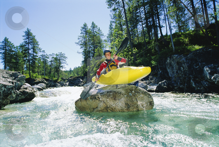 Kayaker perched on boulder in river stock photo, Kayaker perched on boulder in river by Monkey Business Images
