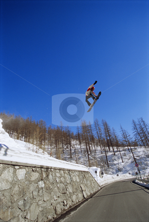 Young man snowboarding stock photo, Young man snowboarding jumping over road by Monkey Business Images