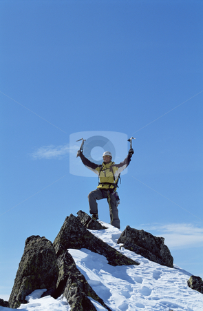 Climber on mountain top stock photo, Young man celebrating reaching the top of a mountain by Monkey Business Images