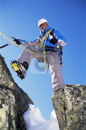 Mountain climbing stock photo, Young man mountain climbing on snowy peak by Monkey Business Images