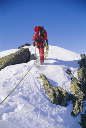 Mountain climber stock photo, Young man mountain climbing on snowy peak by Monkey Business Images
