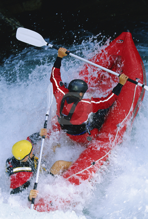 White water rafting stock photo, Two people paddling inflatable boat down rapids by Monkey Business Images