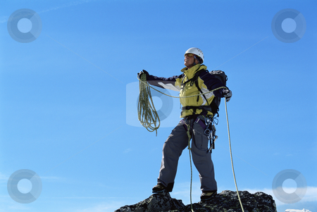 Mountaineer stock photo, Mountaineer on top of mountain summit by Monkey Business Images