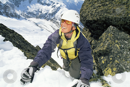 Mountaineer climbing stock photo, Mountaineer climbing a steep slope. by Monkey Business Images