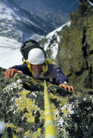 Mountaineer climbing stock photo, Mountaineer scaling snowy rock face by Monkey Business Images