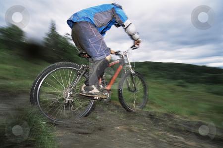 Mountain biking stock photo, Young man mountain biking by Monkey Business Images