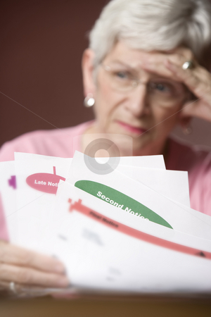 Senior woman with bills and notices stock photo, Upset senior woman with many bills and notices by Scott Griessel