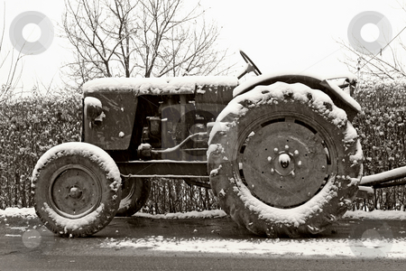 Old tractor in winter stock photo, Black and white photograph of classic old tractor in winter by Mark Yuill